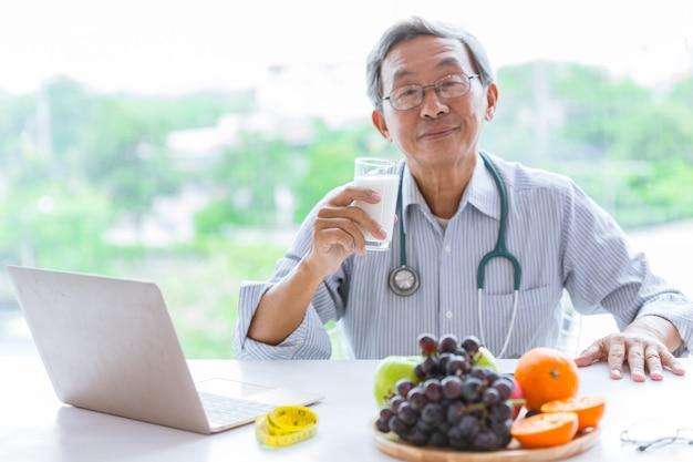 Médico senior bebe consejero de leche comiendo alimentos saludables para la dieta
