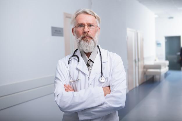 Médico senior experimentado mirando a la cámara con confianza