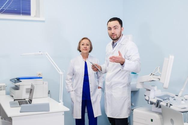 Médico senior hablando con joven asistente de pie en la oficina ginecológica