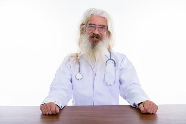 Médico senior hombre barbudo con anteojos en la mesa de madera
