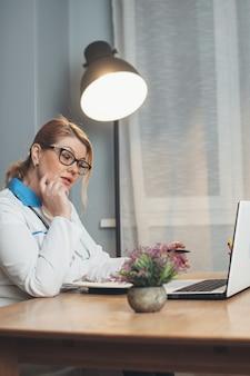 El médico senior que trabaja desde casa tiene una reunión en línea con el paciente usando una computadora portátil y vistiendo ropa y herramientas médicas