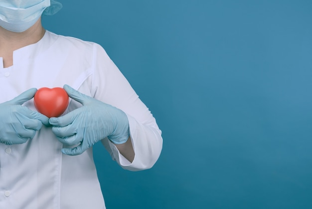Médico de sexo femenino con una bata blanca, una máscara y sostiene un corazón rojo, el concepto de donación y amabilidad, espacio de copia