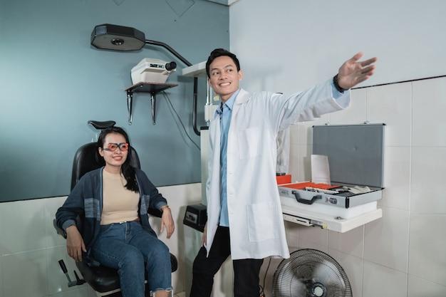 Un médico de sexo masculino está explicando el proceso de un examen de salud ocular a una paciente en una habitación de la clínica oftalmológica
