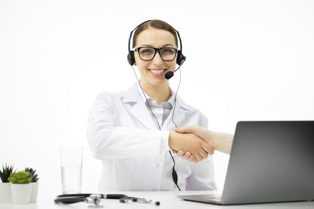 Médico sexy e inteligente con auriculares ofrece consulta en línea para el paciente en la computadora