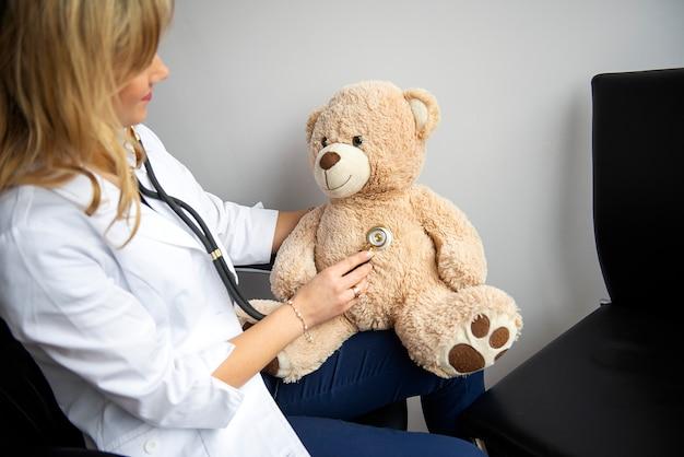 Médico sonriente amable pediatra examinando osito de peluche con ayuda de estetoscopio