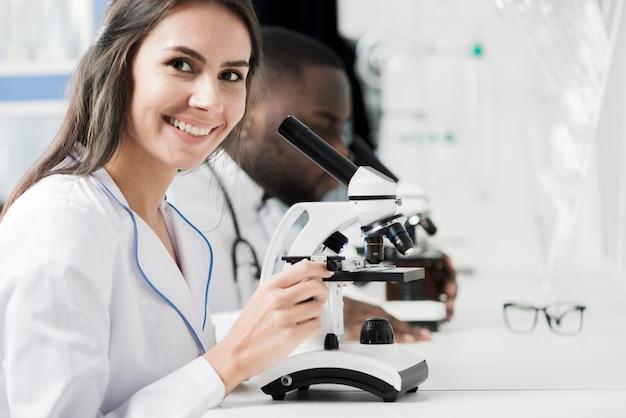 Médico sonriente con microscopio