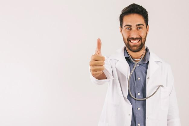 Médico sonriente posando con el pulgar en alto