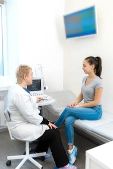 Un médico con una sonrisa en su rostro consulta a un paciente después de un diagnóstico por ultrasonido.