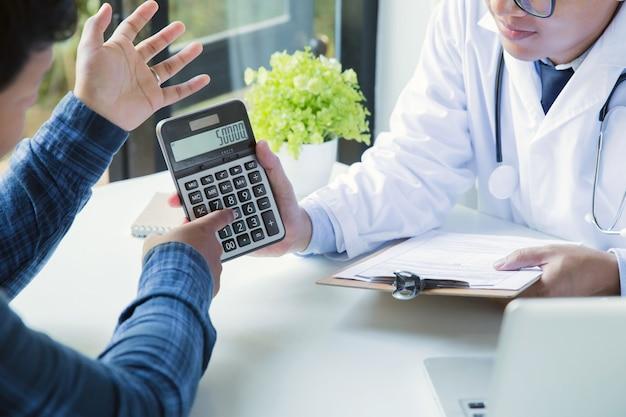 Médico sosteniendo la calculadora para explicar los gastos al paciente.