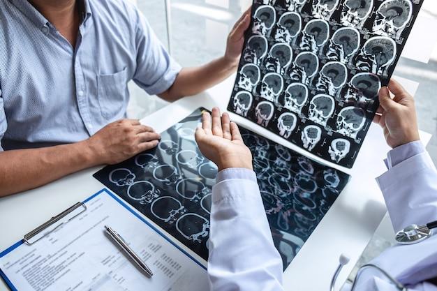 Médico sosteniendo y mirando una película de rayos x que examina el cerebro mediante una tomografía computarizada del paciente y analiza el resultado mientras discute la explicación del problema médico.