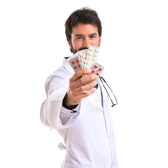 Médico sosteniendo pastillas sobre fondo blanco