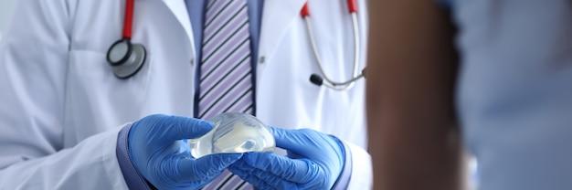 El médico sostiene un implante mamario en sus manos.