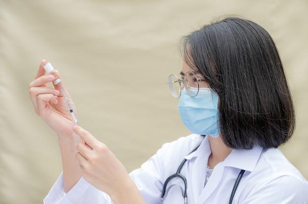 El médico sostiene una jeringa y estaba a punto de vacunar al paciente en la clínica para evitar la propagación del virus.