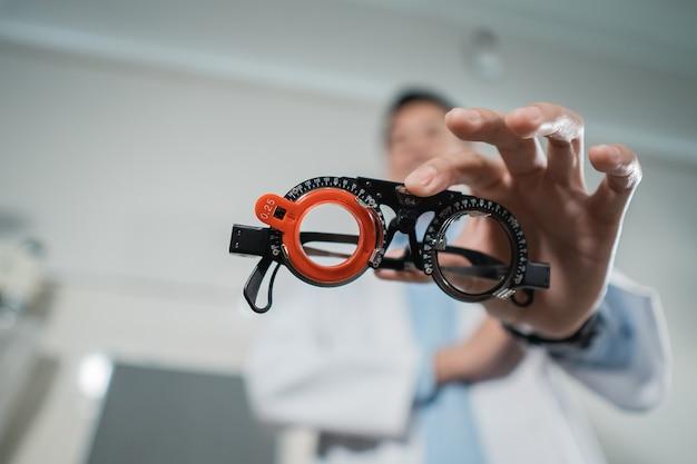 Un médico sostiene un marco de prueba en una clínica oftalmológica contra la pared de las condiciones de la habitación de la clínica