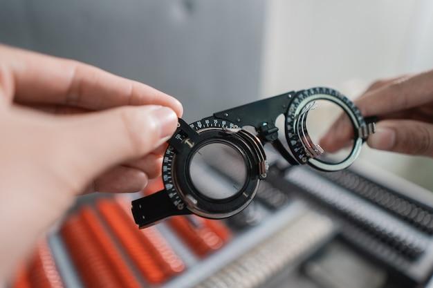 Un médico sostiene un marco de prueba de eje ajustable en una clínica oftalmológica con antecedentes médicos y una caja de almacenamiento