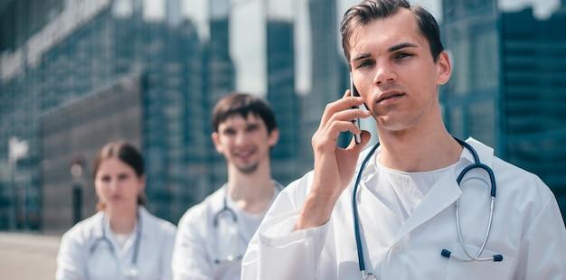 Médico con un teléfono inteligente de pie cerca de un edificio del hospital