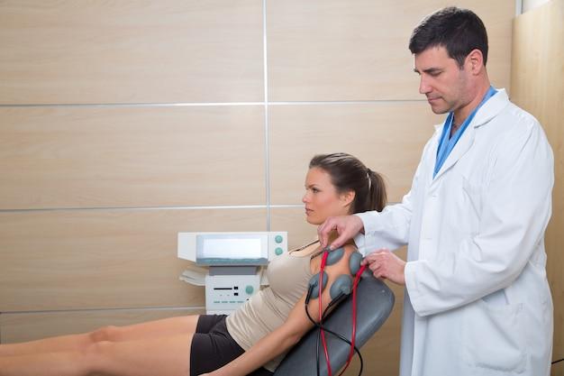 Médico terapeuta revisando electroestimulación muscular a mujer.
