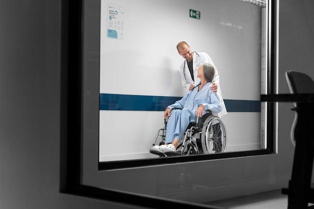Médico de tiro completo y paciente en silla de ruedas