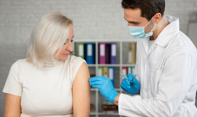 Médico de tiro medio administrando la vacuna
