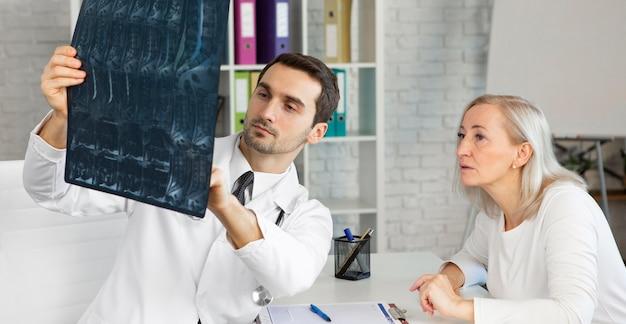 Médico de tiro medio explicando la radiografía