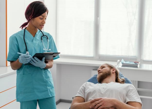 Médico de tiro medio hablando con el paciente
