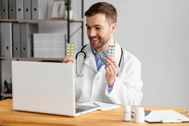Médico de tiro medio mostrando pastillas