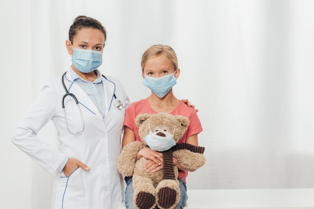 Médico de tiro medio y niño con oso