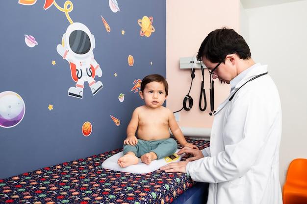Médico de tiro medio pesando a un bebé.