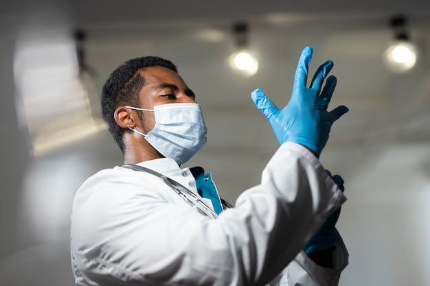 Médico de tiro medio poniéndose guantes