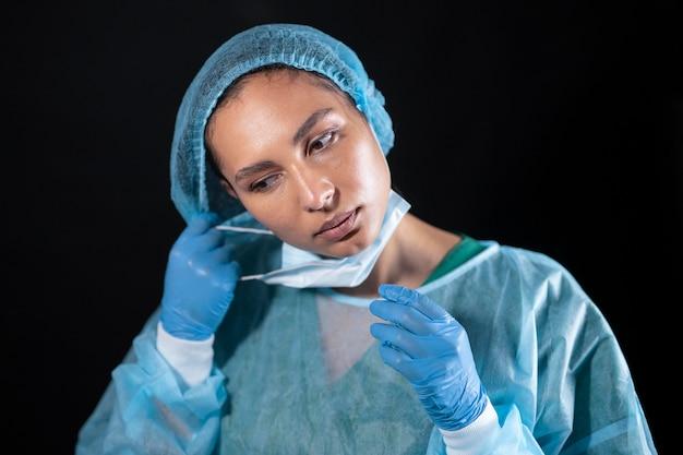 Médico de tiro medio quitándose la máscara