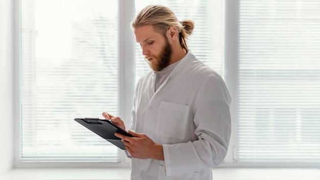 Médico de tiro medio tomando notas