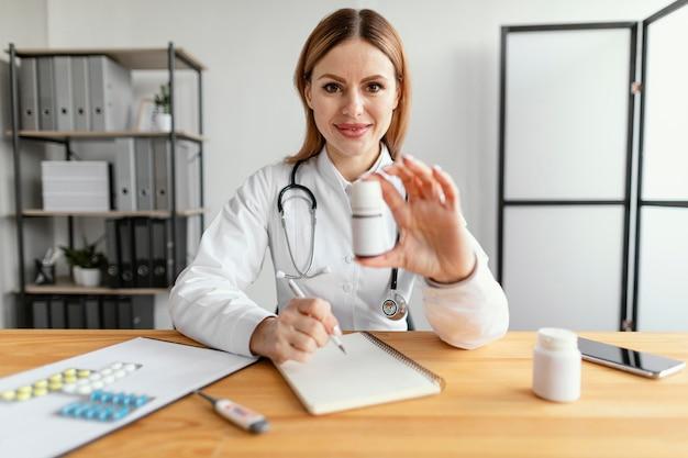 Médico de tiro medio en el trabajo con la medicina