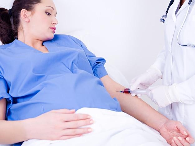 El médico toma sangre en el análisis de una vena de la mujer embarazada