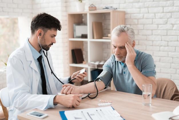 Médico con tonómetro mide la presión sanguínea del anciano.