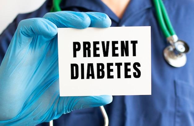 Un médico con un traje azul sostiene una tarjeta con el texto prevenir la diabetes. concepto médico.