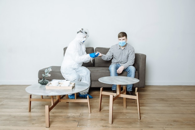 Un médico con traje de protección mide el nivel de oxígeno de un paciente con un oxímetro de pulso para detectar los síntomas del coronavirus covid-19