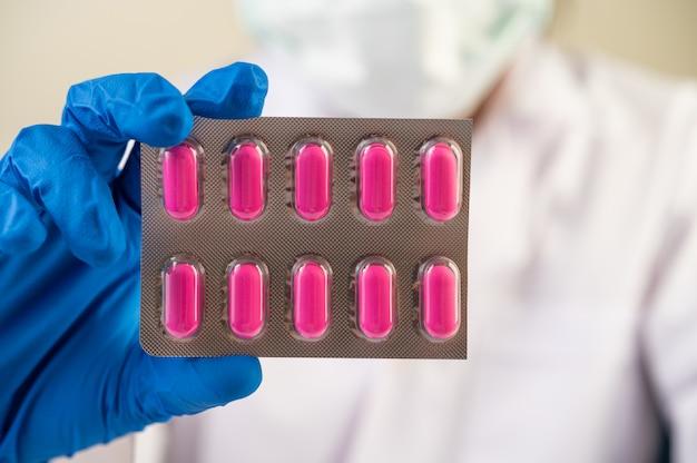 Médico use guantes y sostenga paneles de medicamentos.