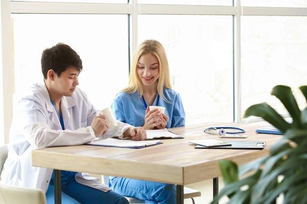 Médico varón y asistente médico femenino bebiendo café durante el descanso en la clínica