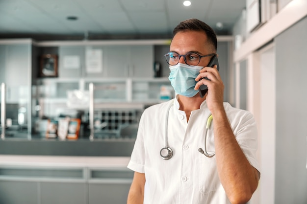 Médico varón atractivo joven con mascarilla utilizando teléfono inteligente para llamadas de emergencia.