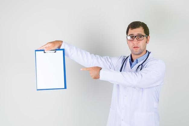 Médico varón en bata blanca, gafas apuntando con el dedo en el portapapeles