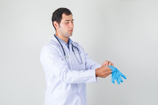 Médico varón en bata blanca con guantes médicos azules y mirando con cuidado