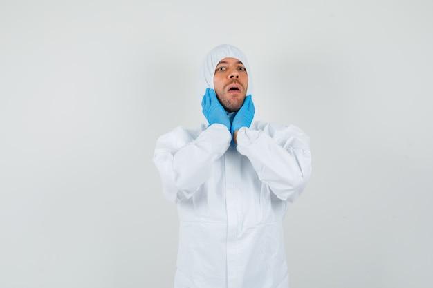 Médico varón con dolor de garganta en traje protector