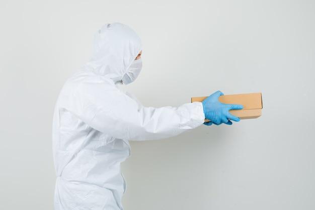 Médico varón entrega caja de cartón en traje protector