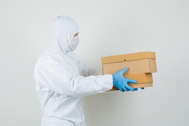 Médico varón entregando cajas de cartón en traje protector