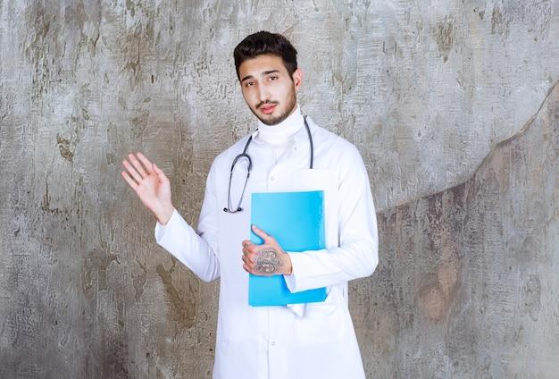 Médico varón con estetoscopio sosteniendo una carpeta azul e interactuando con la persona que lo rodea.