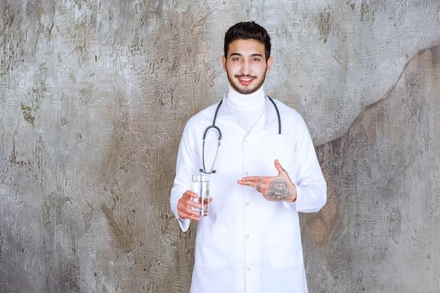 Médico varón con estetoscopio sosteniendo un vaso de agua pura.