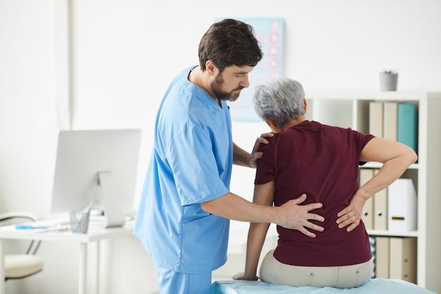 Médico varón examinando la espalda de la mujer mayor durante su visita al hospital