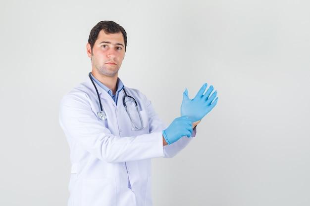 Médico varón con guantes médicos azules en bata blanca y mirando con cuidado