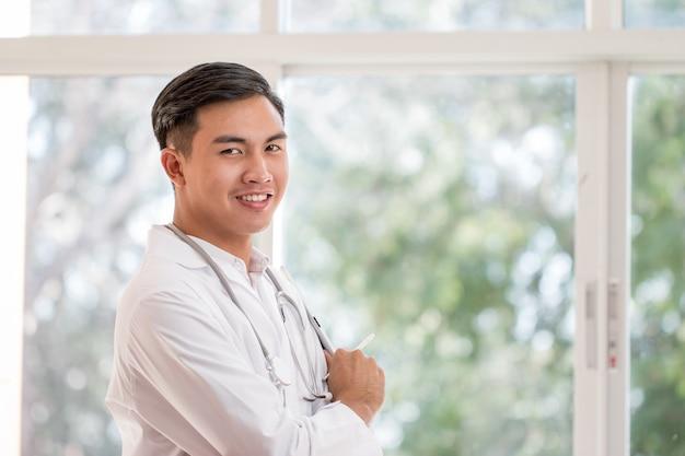 Médico varón inteligente con tablet pc con suite de bata blanca