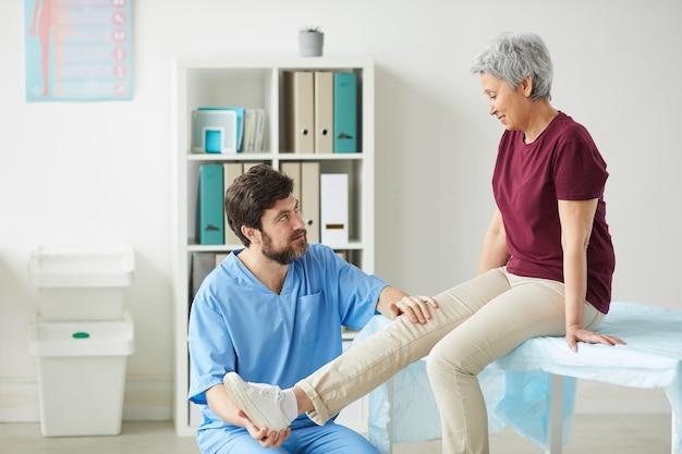 Médico varón maduro examinando la pierna de la mujer mayor durante el examen médico en el hospital
